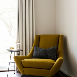 Guest bedroom corner with yellow reupholstered chair with a round side table