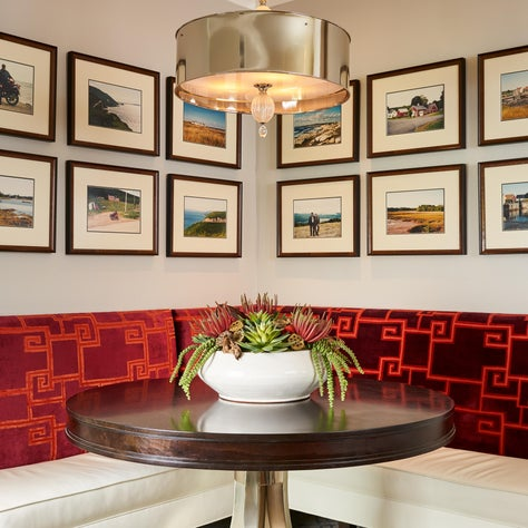 A gallery wall from the client's favorite vacations hang above the banquette.