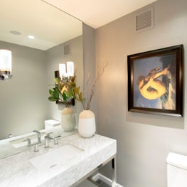 Hollywood bathroom with marble surfaces, rich gray walls and classic art