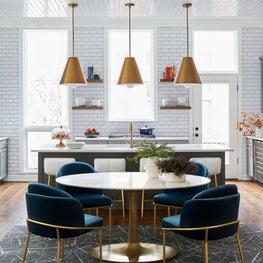 White kitchen with subway tile backsplash, quartz countertops, marble dining table, oversized pendants, large windows, blue chairs