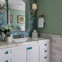 This bathroom is adorned in vibrant turquoise wall tiles and patterned wallcovering.