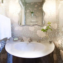 A half-bath with a locally made bespoke vanity, marbled countertop and rose patterned wallpaper.