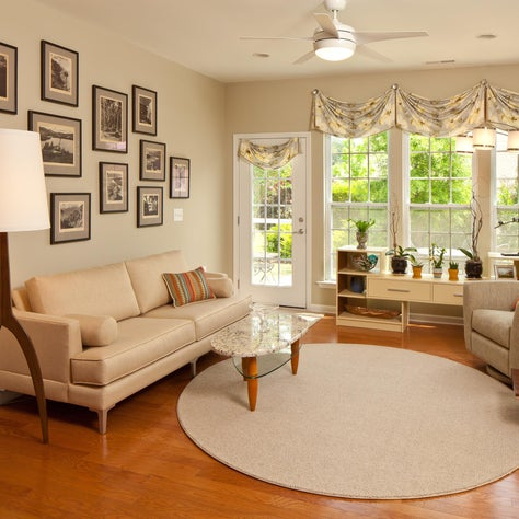 Airy sunroom with neutral color palette, round rug and photography wall grouping