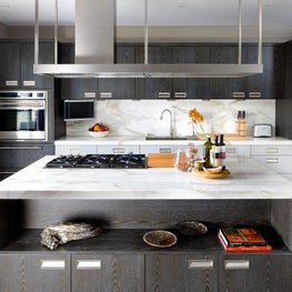 Contemporary dark wood kitchen with marble countertops and a backsplash.