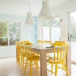 Hamptons beach house bright white kitchen with yellow scandinavian dining chairs