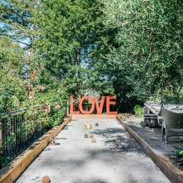 Verdant bocce ball court with LOVE sculpture