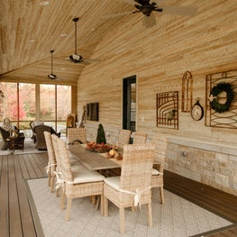 Three-seasons porch, woven chairs, area rug, wood floor, wall art, dining table