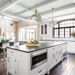 White kitchen coffered ceiling arched metal window table island with turned legs
