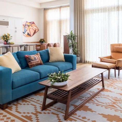 A contemporary, custom made American walnut coffee table pairs with a sofa inspired by the sensibilities of William Morris. The peacock blue sofa textile is incredibly sturdy, perfect for a busy family with young children and dogs.