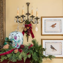 Greenery lends itself as timeless holiday decor with decorative sconce above.