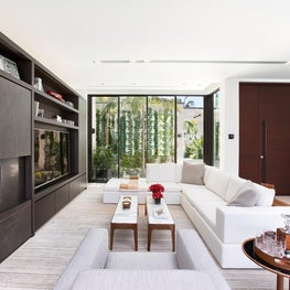 This dark custom fireplace contrasts this light, white modern living room.