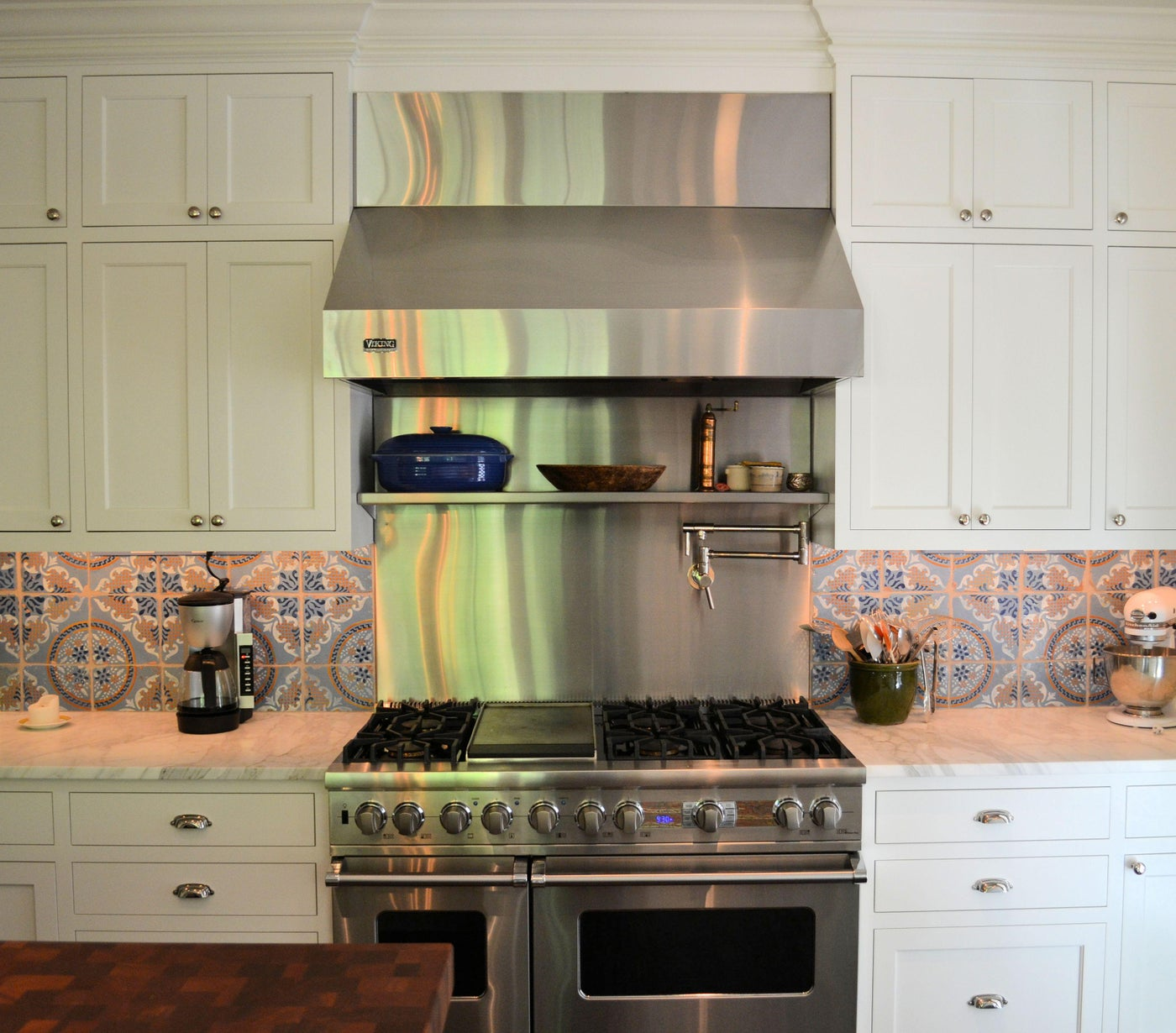 Blue and white kitchen, white cabinets and blue Mediterranean-style backslash