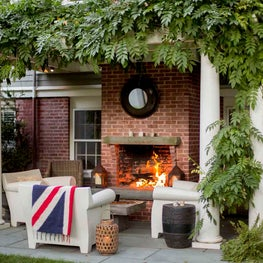 Trellis-covered Outdoor Living Space with Fireplace and Philippe Starck Chairs