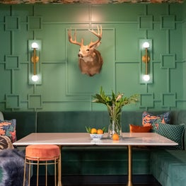 A Mid-Century Country Club inspired basement banquette with custom millwork, seating and family heirloom taxidermy.