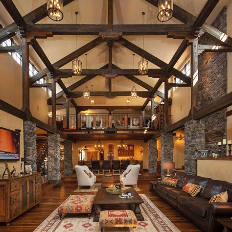 Double height great room with stone and wood construction, iron chandeliers