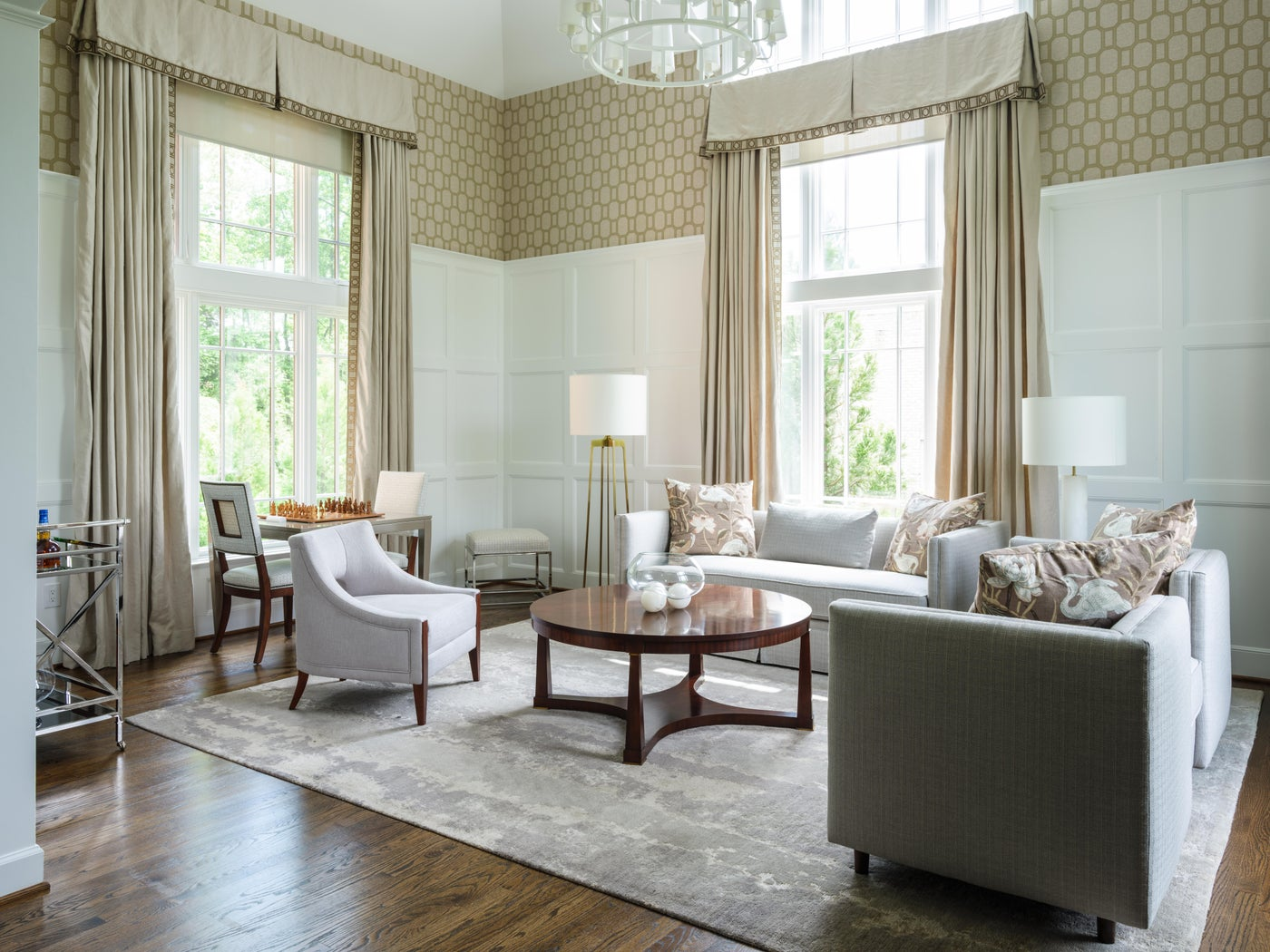 Conservatory with paneled wainscoting, geometric wallcovering and game table.