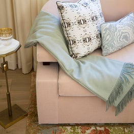 Rose colored velvet sofa with small marble top side table