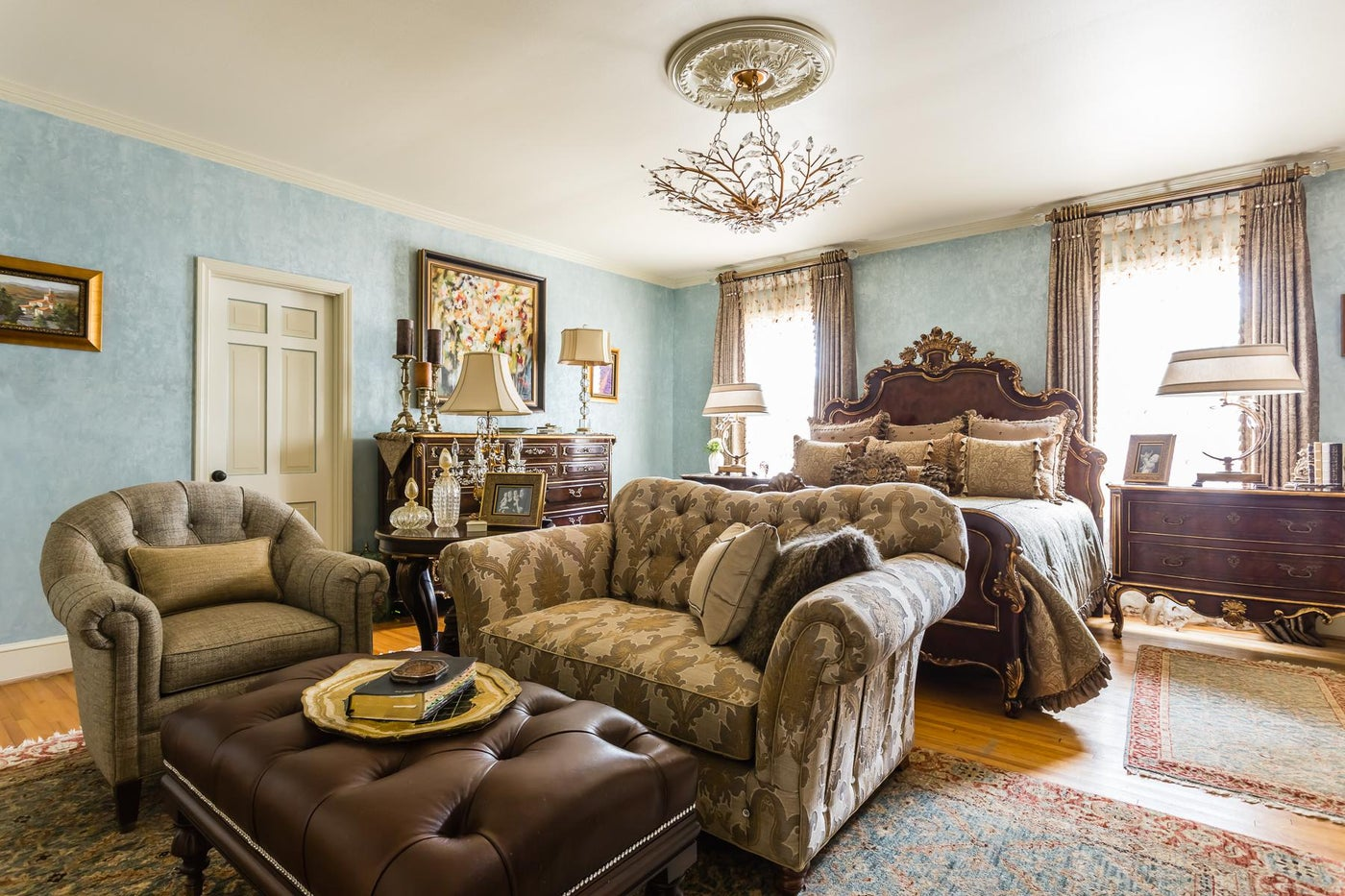 Expansive master bedroom with gilded furniture, tufted seating and crystal lamps