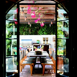 Arched steel and glass doors leading onto the pergola