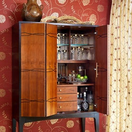 In this dramatic, worldly dining room, an inlaid-wood bar cabinet holds cocktail accoutrements and stands ready for the owners' next intimate gathering with friends and family.