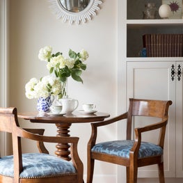 Interior sitting room with charming round table and blue chairs