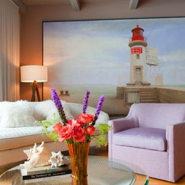 Seating area in sunrise colors, large lighthouse painting, Platner coffee table.
