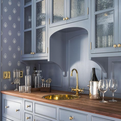 Butler's pantry with blue cabinets, textured glass, and wooden countertop
