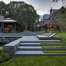 Terraced pool deck with lawn stairs leads to outdoor pavilion & renovated home