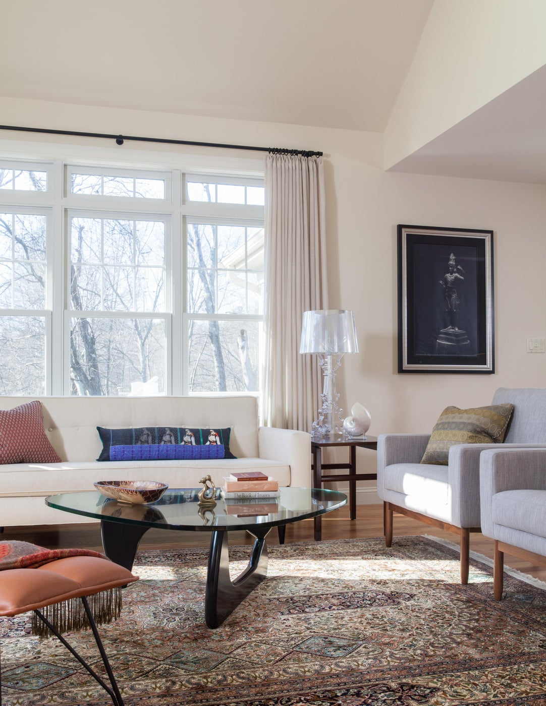 Glasstop coffee table maximizes view of traditional silk rug