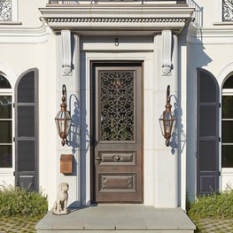 Carved stone pilasters and corbels, hand carved wood door, intricate iron screen