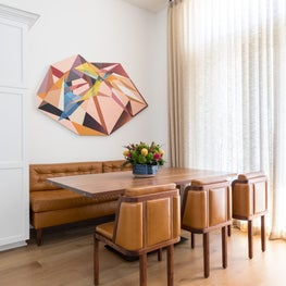 The solid walnut dining table was handmade by local artisans, especially for this project. The powder-coated steel base provides support and stability. Artwork by Kevin Moore hangs above the dining area creating a focal point.