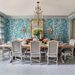 Colorful dining room with floral wallpaper, striped drapes & antique lighting