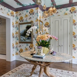 A painted pergola, natural elements, and floral wallpaper bring the outdoors in.
