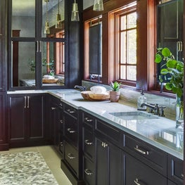 A Modern Craftsman inspired primary bathroom uses custom mirrors to maximize vanity storage space.