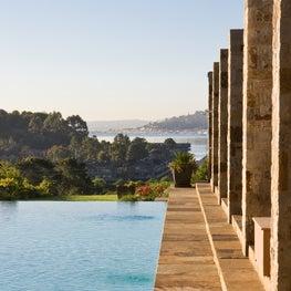 Stone Pergola steps down into Infinity Edge Pool overlooking Bay