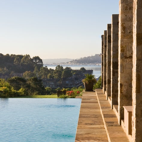 Stone Pergola steps down into Infinity Edge Pool overlooking Bay