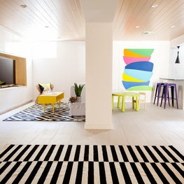 Modern finished basement with pops of art and colorful furniture