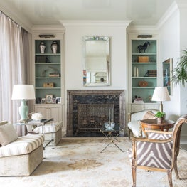 Beveled mirror amplifies this narrow living room