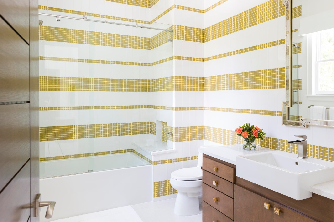 Horizontal stripes of gold and white tile make a bold statement in this bathroom