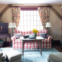 Antiques and a blend of patterned fabrics create a room with a cozy ambiance.