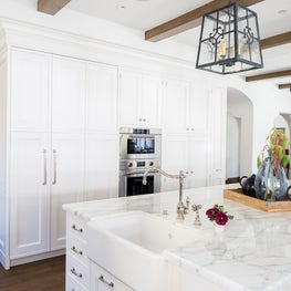 Large island with beautiful marble countertop and farmhouse sink.