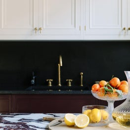 European Style Kitchen with two tone cabinets, marble island, and brass fixtures
