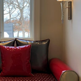 Red & charcoal window seat, red & black pillows, wall sconce, gold accents