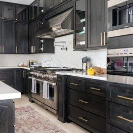 A gorgeous and functional kitchen with black stained cabinets, white floors, gold drawer pulls, and stainless steel appliances