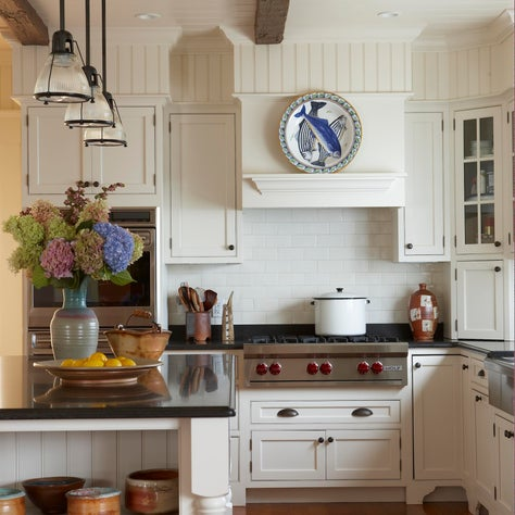 A classic kitchen has a country vibe by adding pottery and a striped area rug.