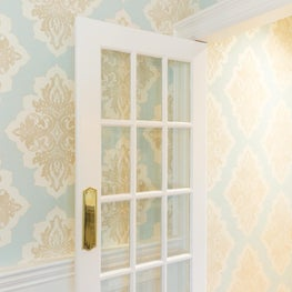 Elegant patterned wallpaper adds glamour to this formal passage.