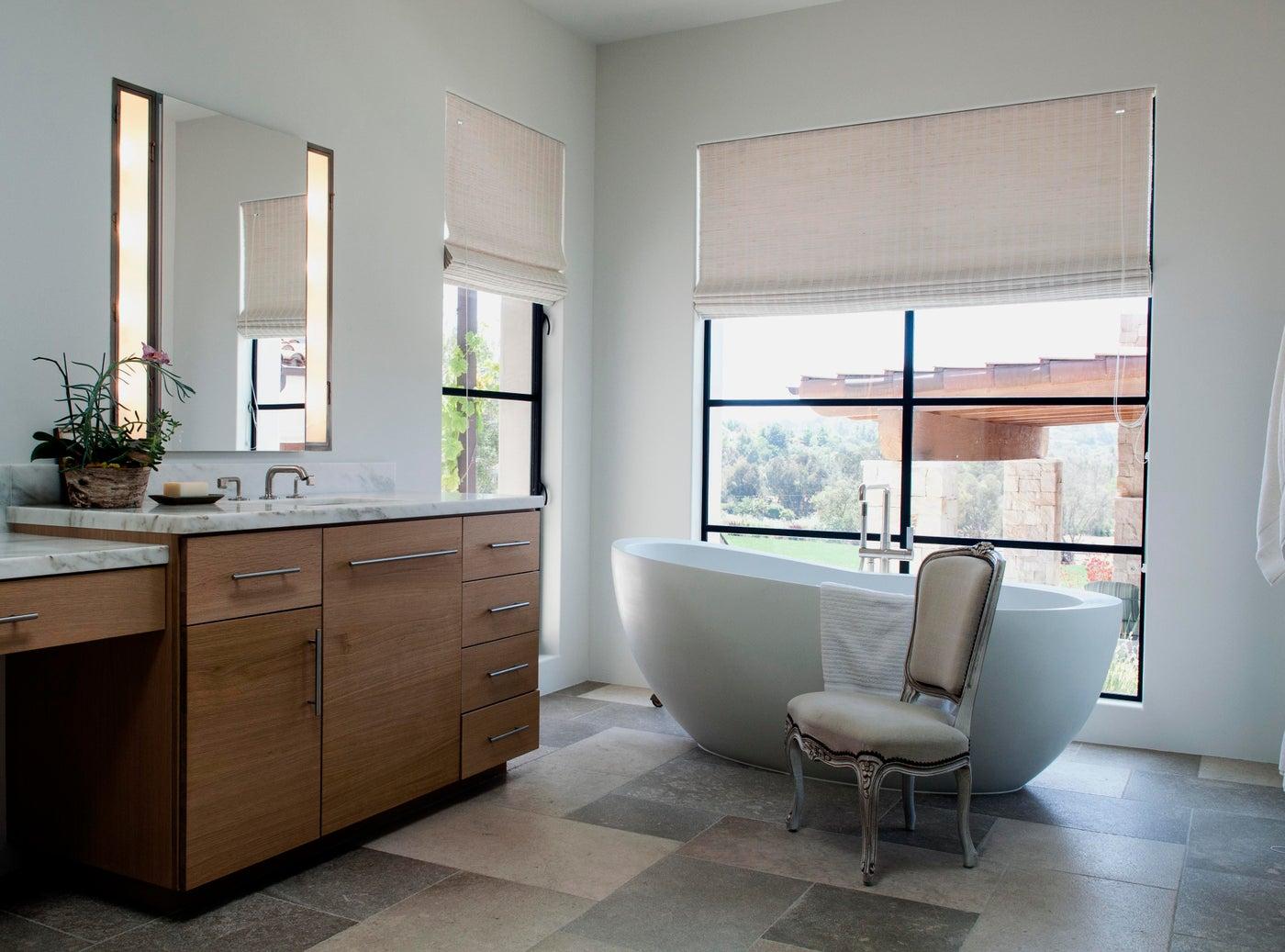 Modern meets Mediterranean in this Rancho Santa Fe master bath, with its sleek Waterworks freestanding tub and antique limestone floor.