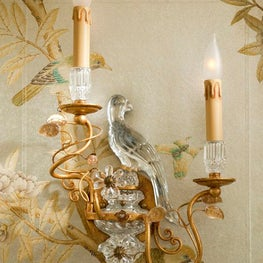 A close up on mirrored sconces designed to echo a powder bath's chinoiserie bird motif