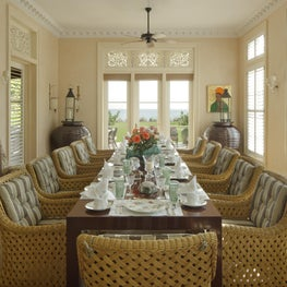 An airy oceanfront Dining Room in Palm Beach.  Carved teak window transoms