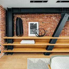 Master Bedroom with Diagonal Bracing on Brick Wall